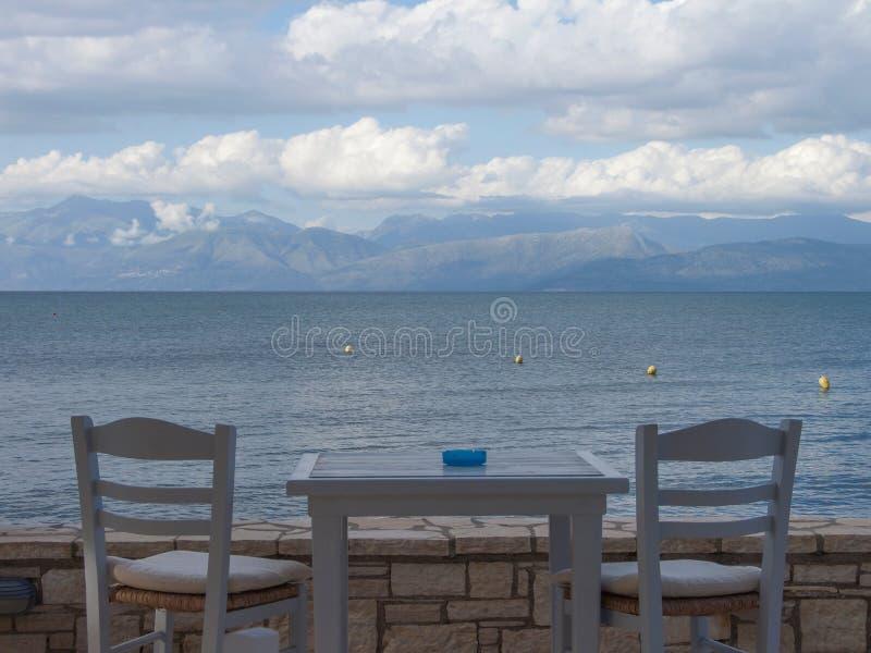 Terrasssikt med den trägråa tabellen och två gråa stolar, hav, cl fotografering för bildbyråer