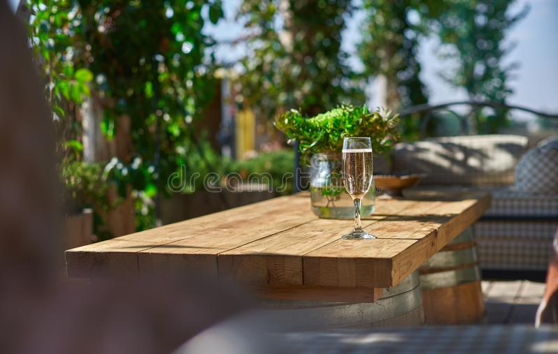 Terraza acogedora con los sofás para el resto, vidrio con champán en una tabla de madera foto de archivo