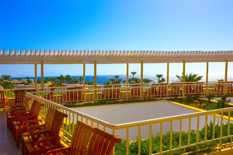 Terraza al aire libre del restaurante que pasa por alto el mar y las palmeras imagen de archivo