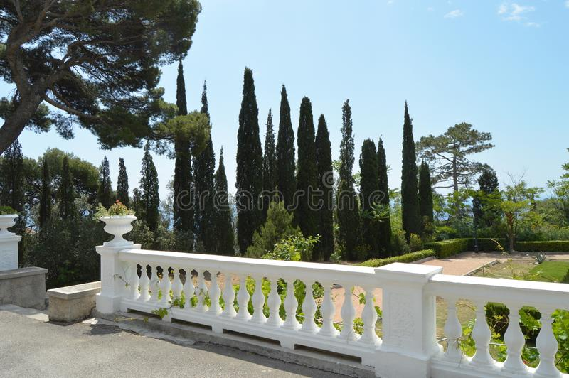 Terraza con la barandilla y las hermosas vistas del parque con los árboles de pino, los árboles de ciprés y las columnas en el fo foto de archivo libre de regalías