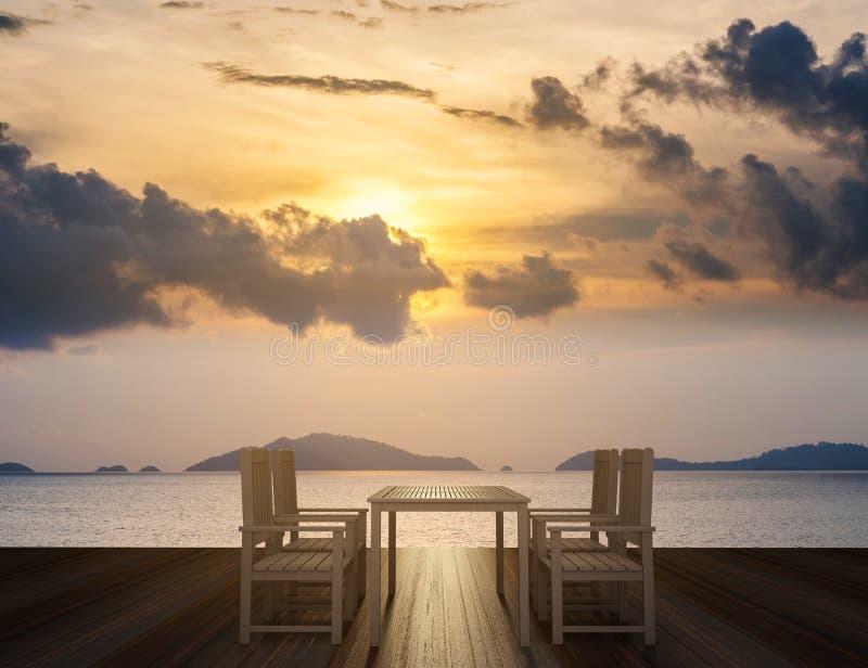 Terraza de madera con la mesa de comedor y sillas en vista al mar tropical en puesta del sol fotos de archivo