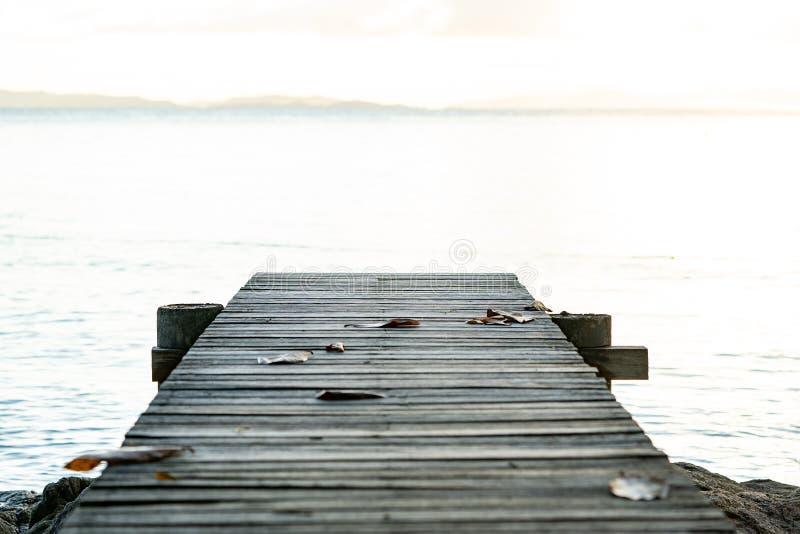 Terraza de madera del vintage en la playa con el mar azul, océano, fondo del cielo imagenes de archivo