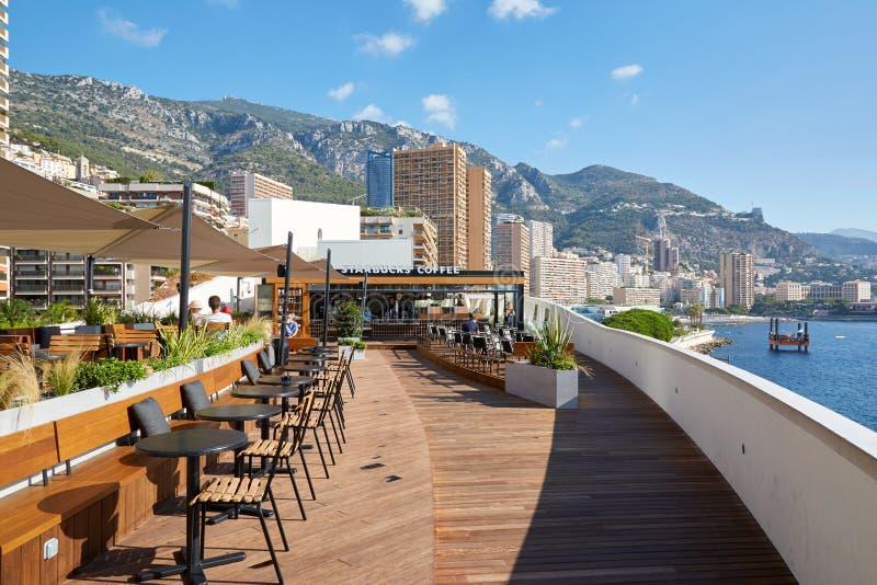 Terraza del café del café de Starbucks en un día de verano soleado con la opinión del mar y de la ciudad en Monte Carlo, Mónaco imagenes de archivo