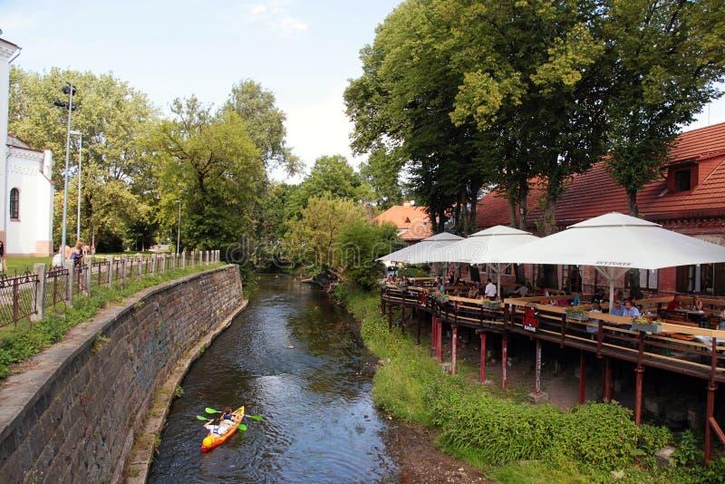 Terraza del café y barco de la canoa en el río Vilnele cerca del neighbo de Uzupis imagenes de archivo