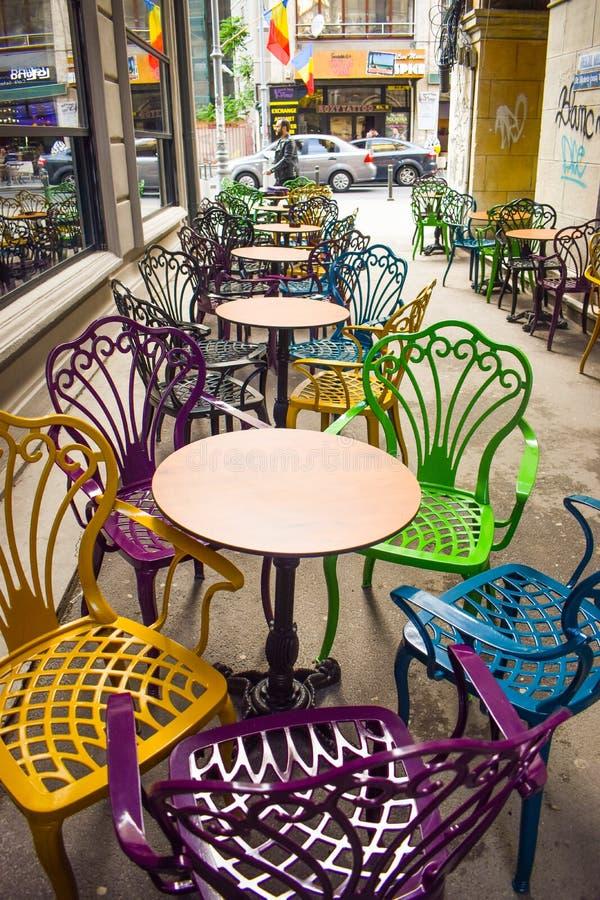 Terraza vacía del vintage en centro de la ciudad histórico con las sillas multicoloras en la acera del pavimento Sillas coloridas fotos de archivo libres de regalías