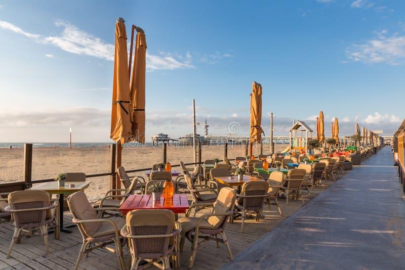 Terrazas a lo largo de la playa holandesa con una visión en el embarcadero de Scheveningen fotos de archivo libres de regalías
