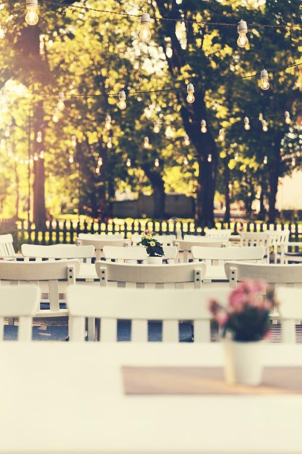 terrazzo all'aperto del giardino del caffè con le luci della corda fotografia stock libera da diritti
