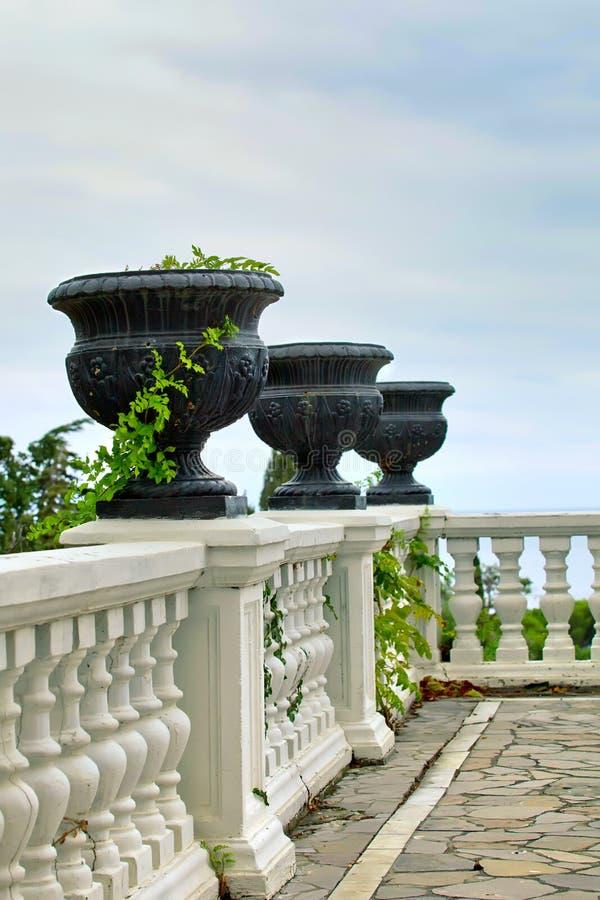 Terrazzo con le inferriate bianche ed i vasi neri immagine stock