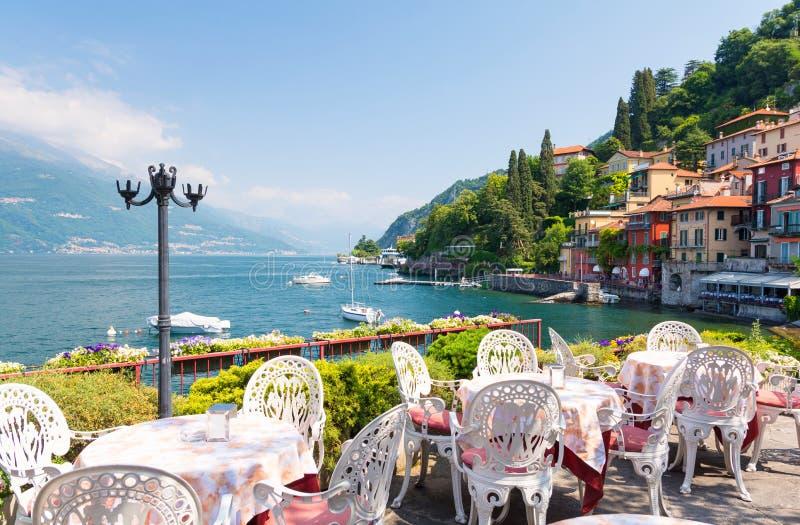 Terrazzo del ristorante con la vista di bella vecchia città di Varenna, lago Como, Italia immagini stock libere da diritti