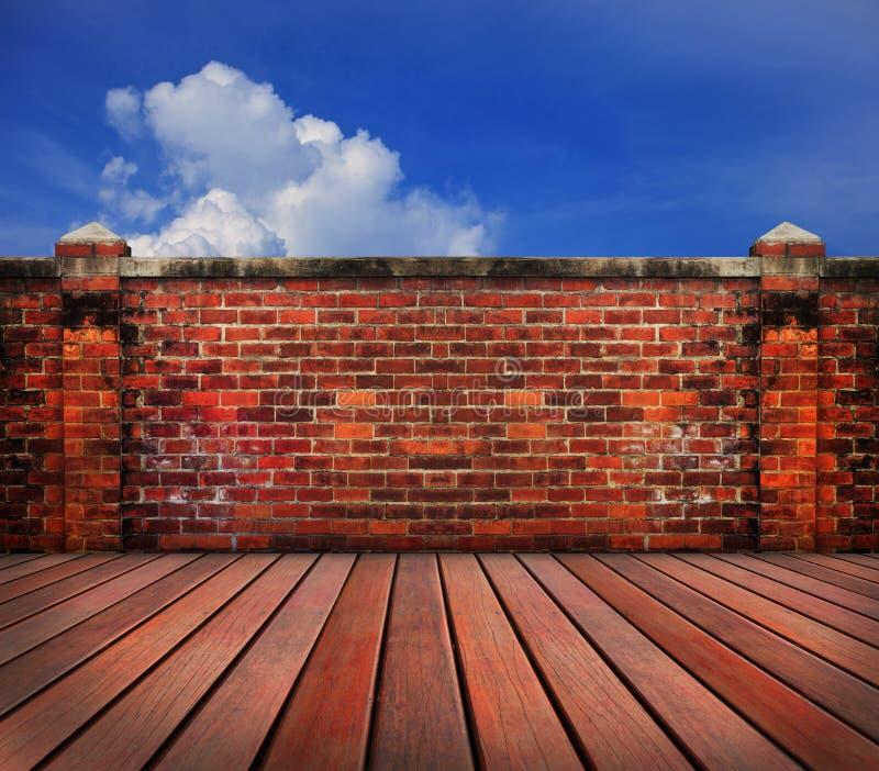 Terrazzo di legno del vecchio muro di mattoni con il backgrund del cielo blu fotografie stock libere da diritti