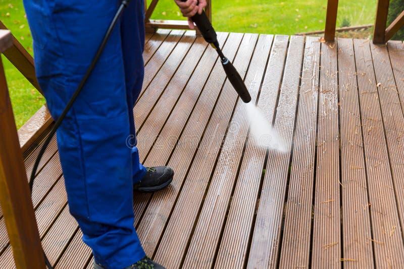 Terrazzo di legno di pulizia con la rondella ad alta pressione immagini stock libere da diritti