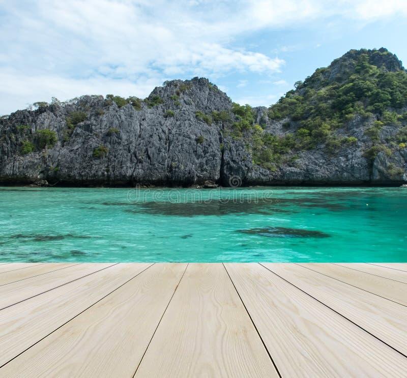 Terrazzo di legno sulla spiaggia con il chiaro cielo, Crystal Clean e la chiara isola grande e del mare nel Myanmar nel fondo di  fotografia stock