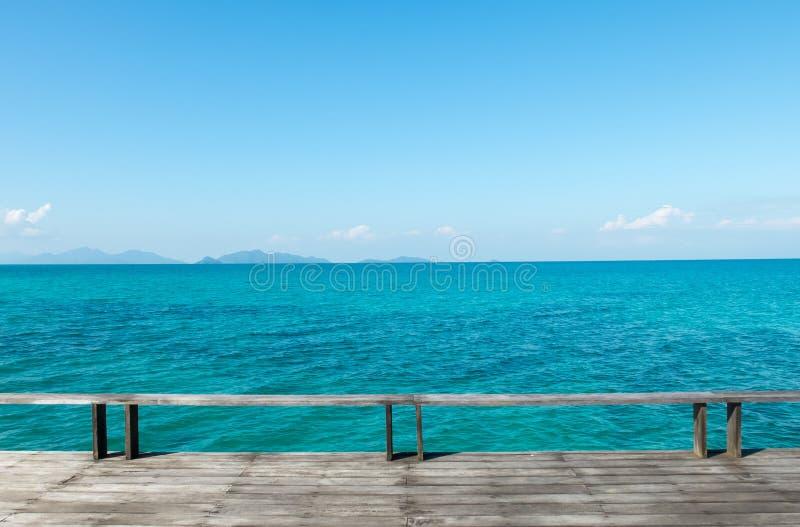 Terrazzo di legno sulla spiaggia con il mare blu ed il chiaro cielo blu fotografia stock libera da diritti