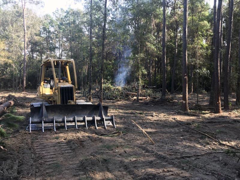 Terre de dégagement de forêt avec le bouteur photographie stock