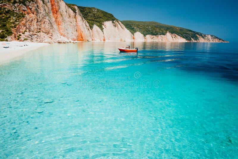 Terre de touristes d'embarcation de plaisance vers beau Pebble Beach blanc à distance avec l'eau de mer bleue claire transparente photos stock