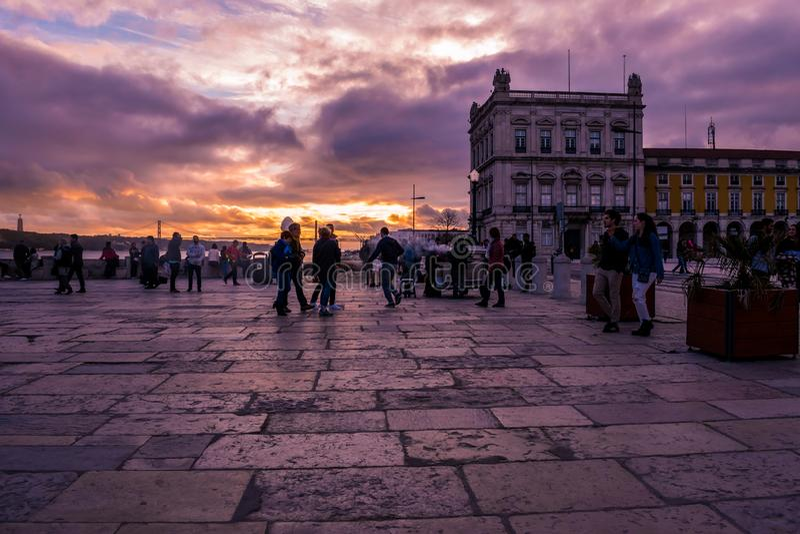 Terreiro gör Paço, Lissabon - mars 17, 2019 - folk som strosar i fyrkanten under en bländande och färgrik solnedgång, Portugal arkivbilder