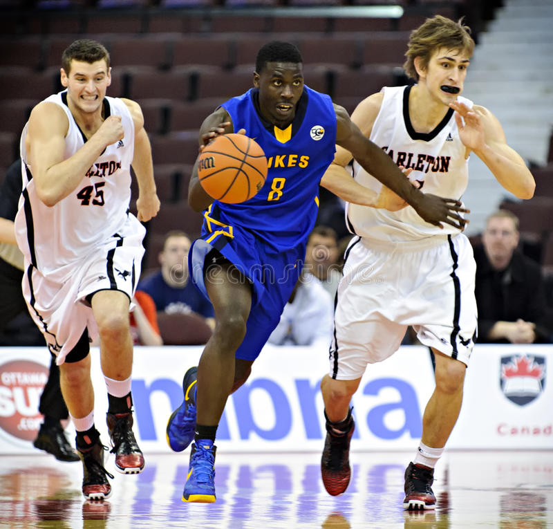 Men's CIS Basketball Finals. Terrell Evans (centre) in action for the Victoria Vikes in their match against the Carleton Ravens at Scotiabank Place, Ottawa on stock photography