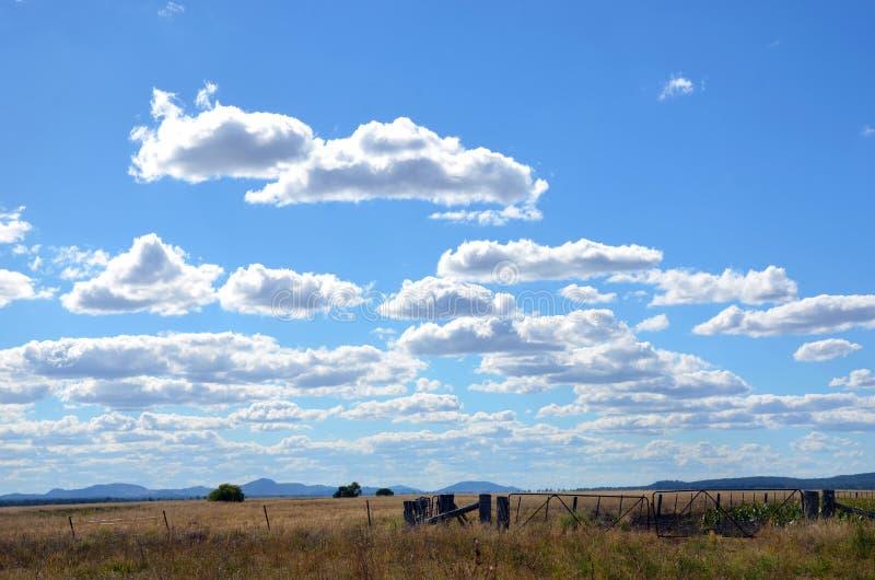 Terreno coltivabile sotto i cieli riempiti nuvola blu fotografie stock