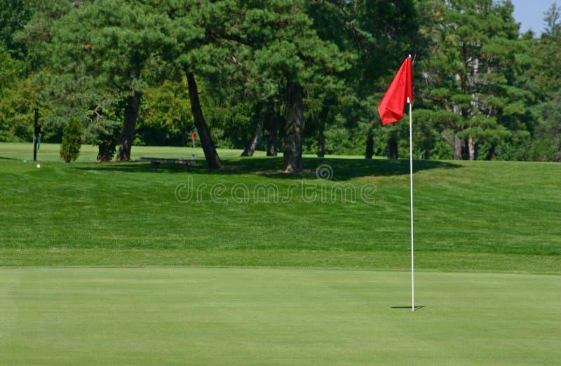 Terreno da golf della bandiera rossa fotografia stock