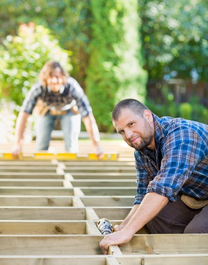 Terreno de construção de Holding Drill At do carpinteiro imagens de stock
