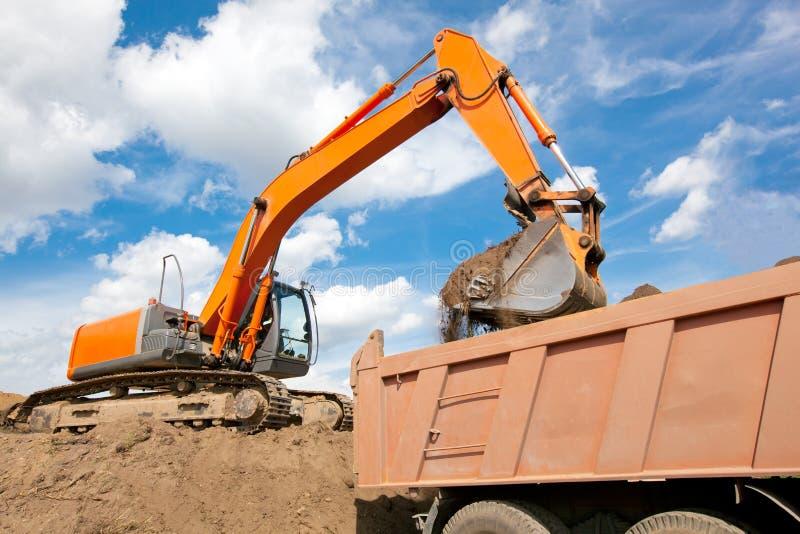 Terreno di caricamento dell'escavatore a cucchiaia rovescia nel corpo dell'autocarro con cassone ribaltabile fotografia stock