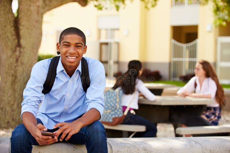 Terreno masculino da escola de Using Phone On do estudante da High School imagens de stock