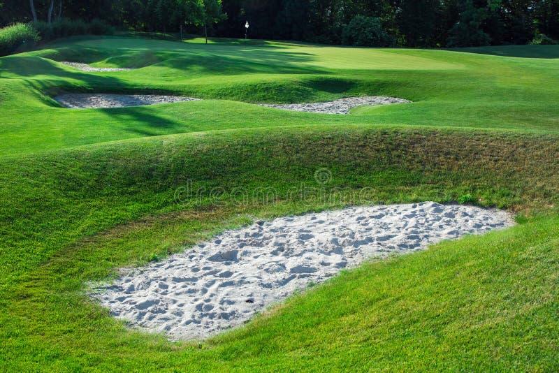 Terreno montañoso del campo de golf con las trampas de arena foto de archivo