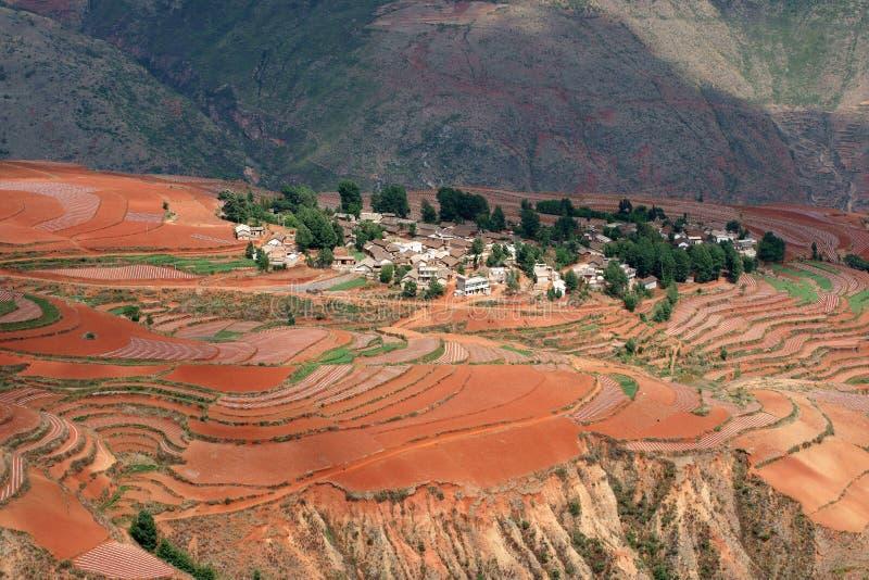 Terres cultivables rouges avec le village dans dongchuan de la porcelaine photographie stock libre de droits