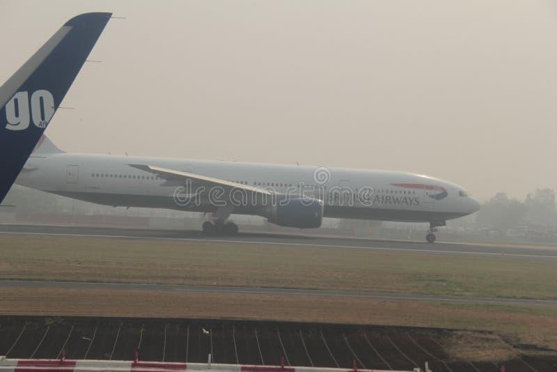 Terres de British Airways dans le brouillard enfumé lourd image libre de droits