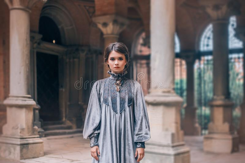 Terrible cold look of nun makes them afraid, a girl with dark hair gathered looks at camera, lady in long, free, simple. Gray velor dress, old columns like in royalty free stock image