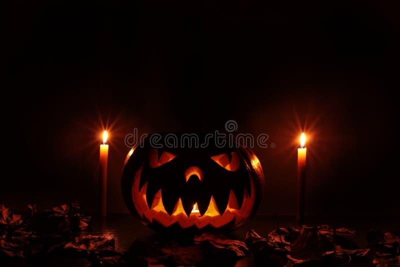 A terrible Halloween pumpkin glowing in the dark stock photo