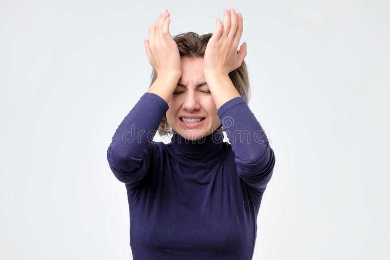 Woman touching her head with hand and making angry face while standing at studio stock image