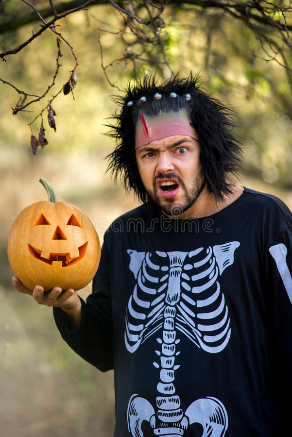 Terrible man. Human zombies holding a pumpkin in her hands. Symbol of the holiday Halloween. Skull. Zombie. Halloween mask. Scary dress for a party on royalty free stock photo