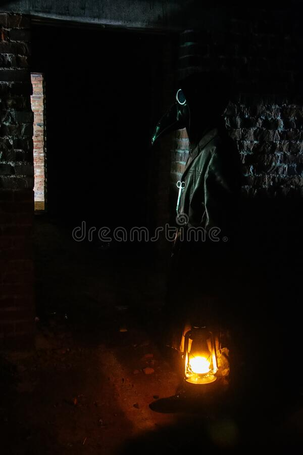 Terrible plague doctor with kerosene lamp. Masked maniac. Halloween and horror concept.  royalty free stock image