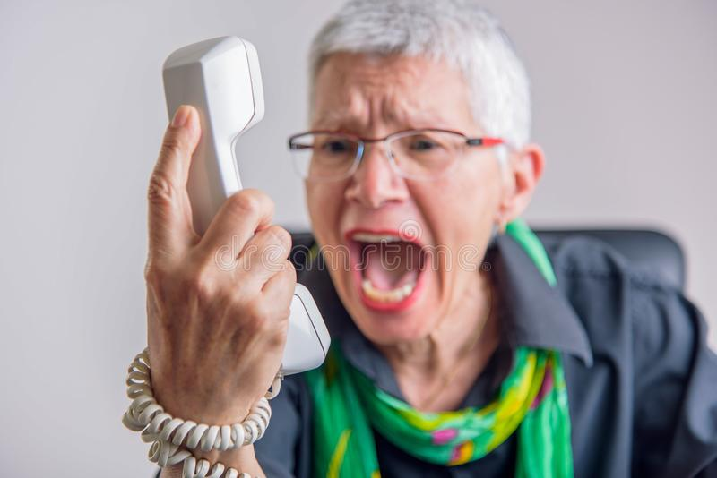 Terrible service, angry senior woman yelling at phone. Angry, enraged senior woman yelling at a landline office phone, unhappy with customer service provided by royalty free stock image