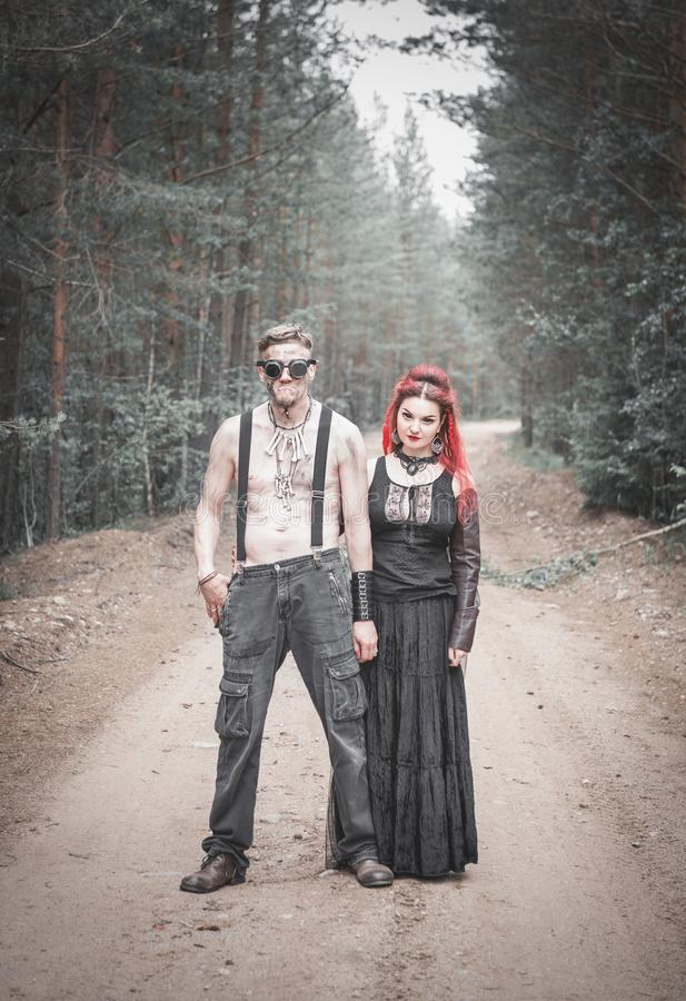 Terrible steampunk man and beautiful witch royalty free stock photography