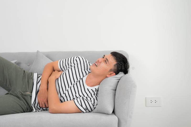 Terrible stomachache. Frustrated handsome young man hugging his belly and keeping eyes closed while lying on the couch at home.  stock photography