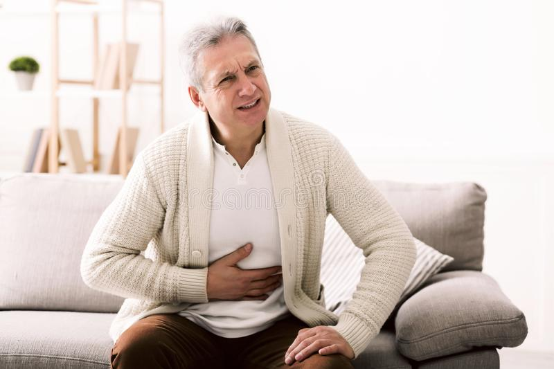 Terrible stomachache. Senior man hugging his belly, suffering from pain royalty free stock photography