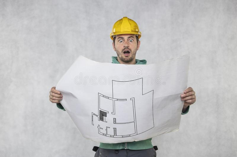 Terrified builder shows apartment plans stock image