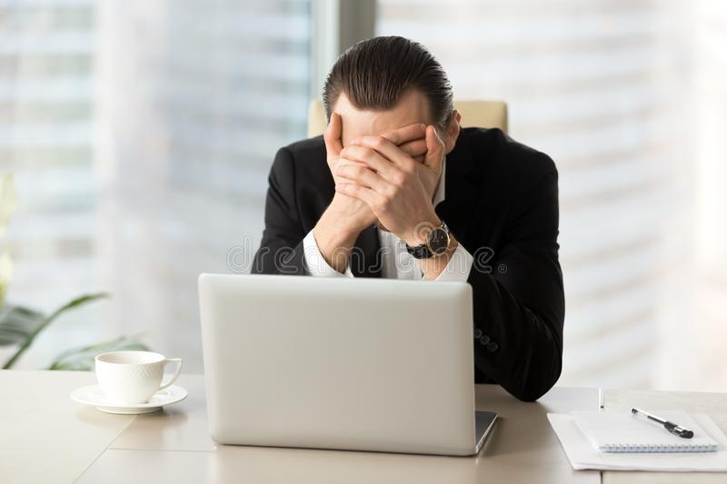 Terrified businessman covering face with hands in front of lapto royalty free stock images