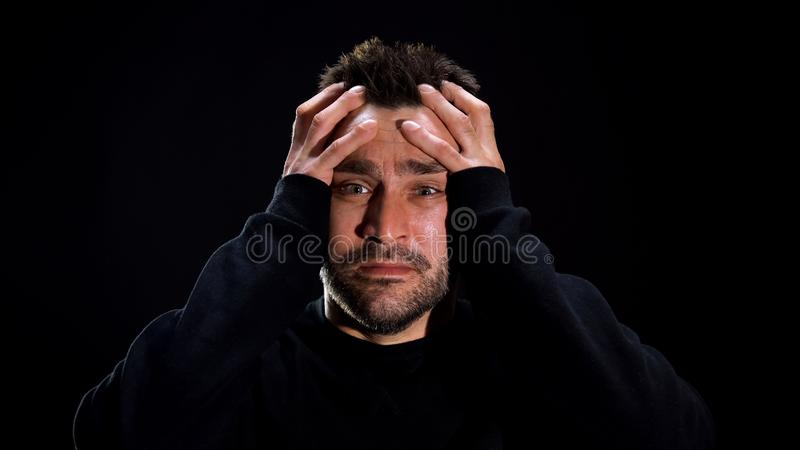 Terrified caucasian man covering head by hands, mental disease, schizophrenia. Stock photo royalty free stock image