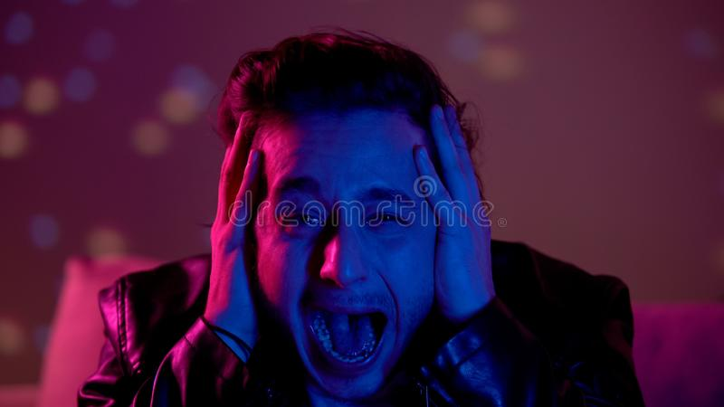 Terrified drunk young man crying and screaming at party, addiction problem. Stock photo royalty free stock image