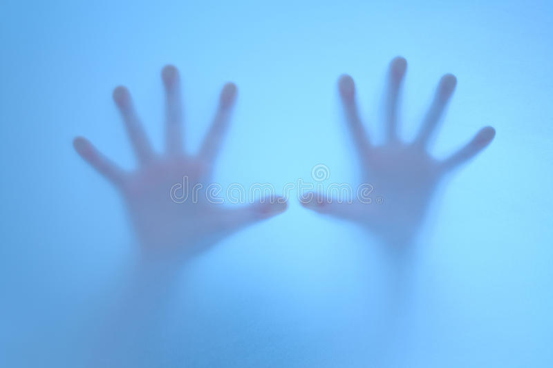 Terrified hands on  frosted glass