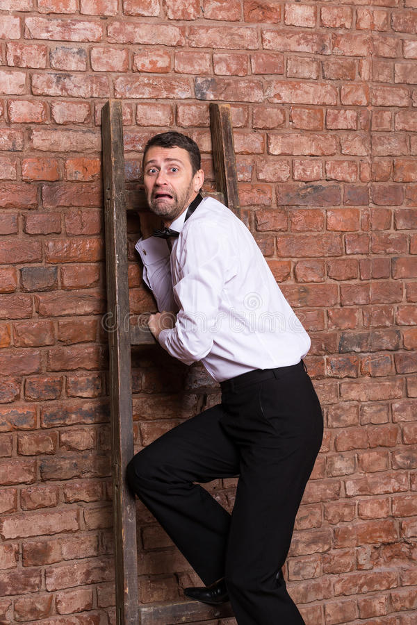 Terrified man trapped at the top of a ladder. Cowering against the brick wall with an expression or dread and fear royalty free stock photography