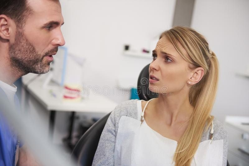 Terrified woman looking at male dentist stock photos