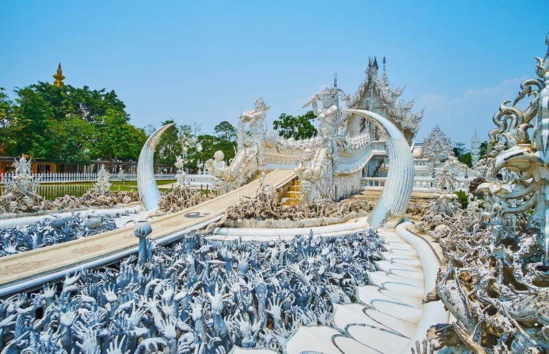 The hell scene in front of Bridge of Rebirth Cycle, White Temple, Chiang Rai, Thailand. Terrifying sculpture of low desires with creepy hands, rising from under stock images