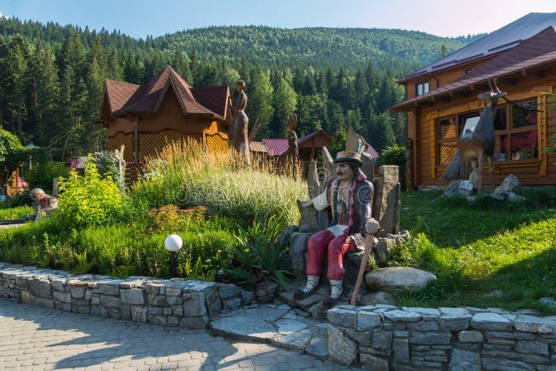 Territoriet av rekreationmitten med en staty av Hutsul i gården mot bakgrunden av gröna berg in royaltyfri fotografi