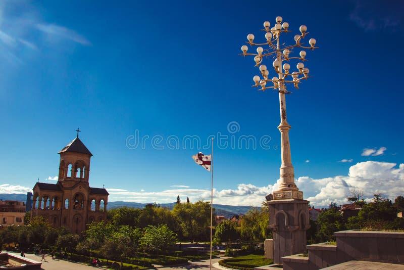 Territorio della cattedrale Tsminda Sameba della trinità santa di Tbilisi Campanile, lampada di via e bandiera georgiana Copi lo  immagine stock