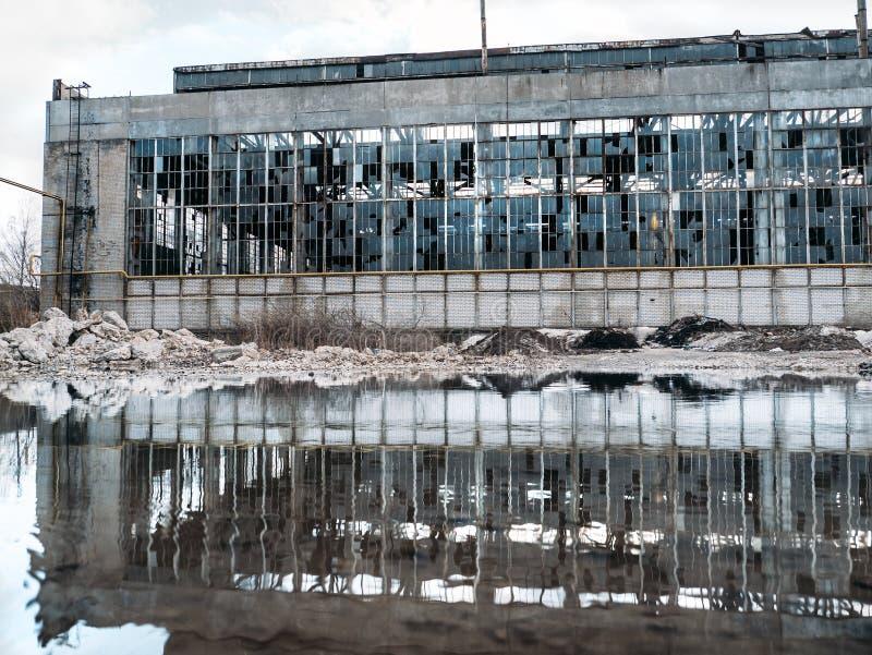 Territorio sommerso della costruzione industriale rovinata abbandonata della fabbrica con la facciata rotta e delle finestre, rif fotografia stock