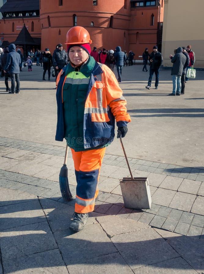 Territoriumlokalvård Kvinna i orange likformig att göra ren trottoaren i området av den röda fyrkanten royaltyfria foton